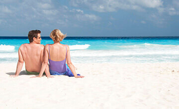 couple sitting on Cancun beach